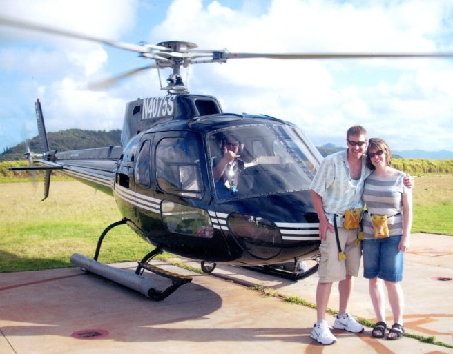 Couple in front of helicopter.